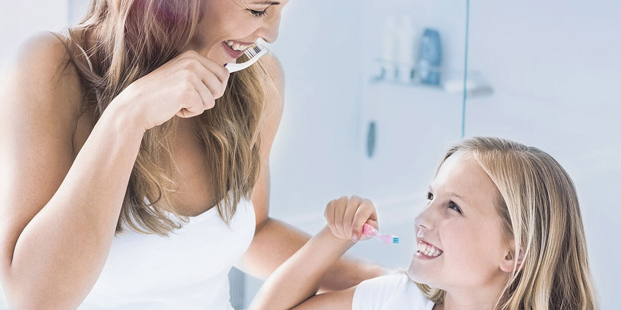 Mother and daugther brushing their teeth