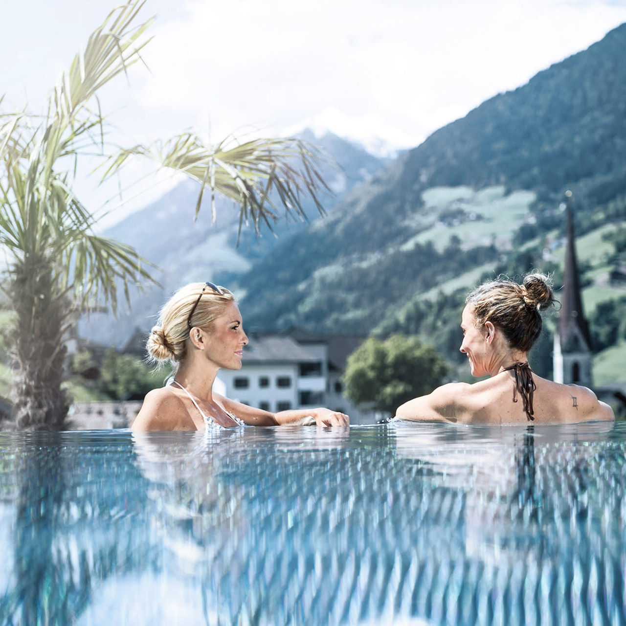 Two women relaxing in swimming pool